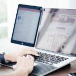 ノートパソコンを操作する腕時計をはめた男性の両腕の小さい画像