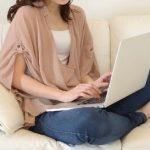 白いソファーでノートパソコンでネットショッピングを楽しむ女性n小さい画像